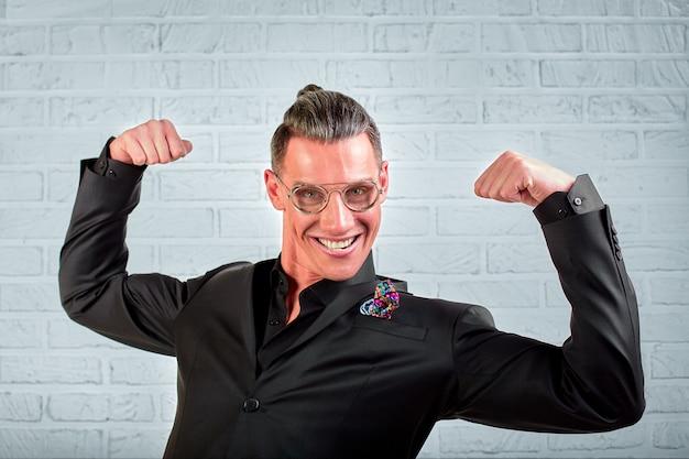 Fechar o retrato de um jovem empresário feliz usando óculos, vestido em um terno preto mostra as mãos legal