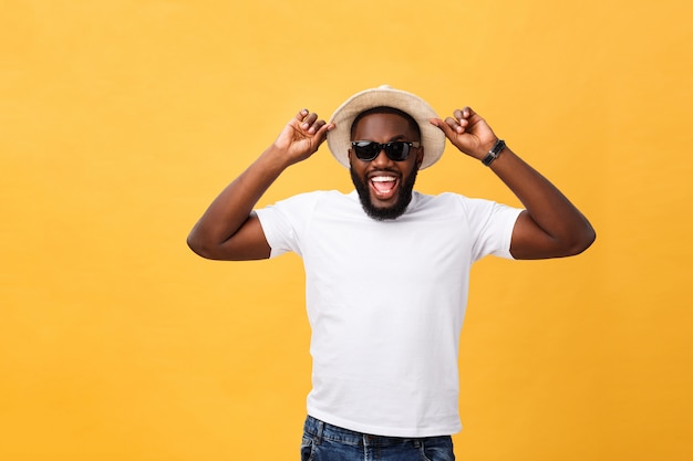 Fechar o retrato de um jovem rindo com as mãos segurando o chapéu isolar sobre fundo amarelo