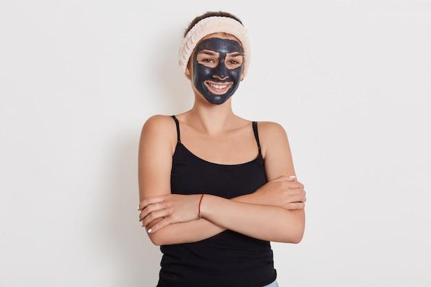 Fechar o retrato de uma jovem fêmea aplica-se a máscara de argila facial caseira, tem uma faixa de cabelo branca na cabeça, sorri alegremente, mantém as mãos dobradas contra a parede branca