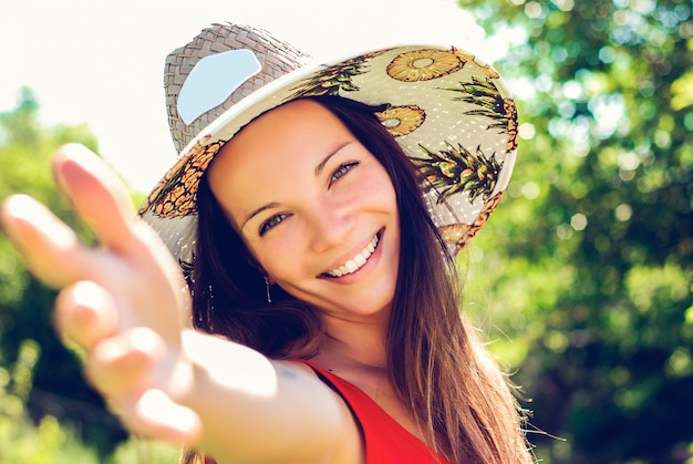Fechar o retrato de uma jovem sorridente com chapéu de palha