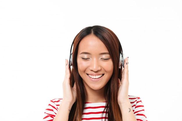 Fechar o retrato de uma menina asiática, ouvir música