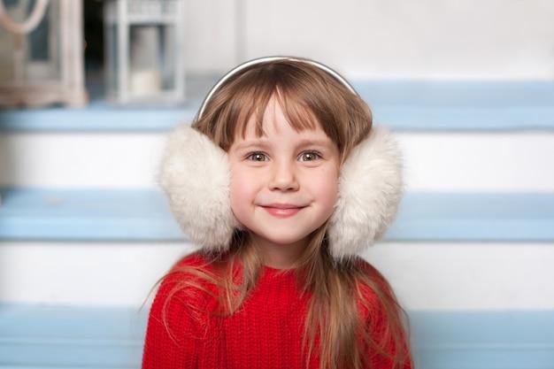 Fechar o retrato de uma menina bonita com uma camisola vermelha, sentado na varanda da casa em um inverno. criança sorridente senta-se em uma escada de madeira na rua. garoto brinca no quintal de inverno perto de casa. véspera de natal