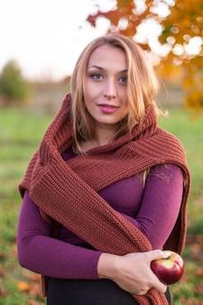 Fechar o retrato de uma menina bonita, envolvida numa camisola quente com maçã na mão