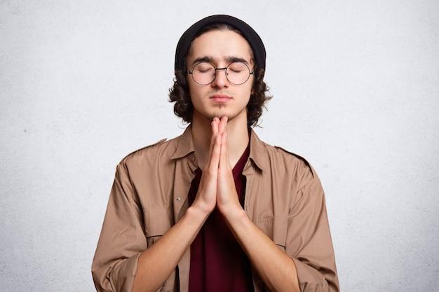 Fechar o retrato do homem concentrado mantém as palmas das mãos pressionadas juntas