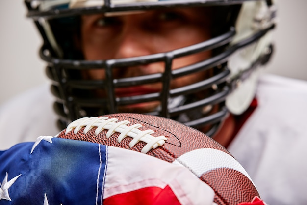 Fechar o retrato do jogador de futebol americano no capacete com bola e bandeira americana, orgulhoso de seu país