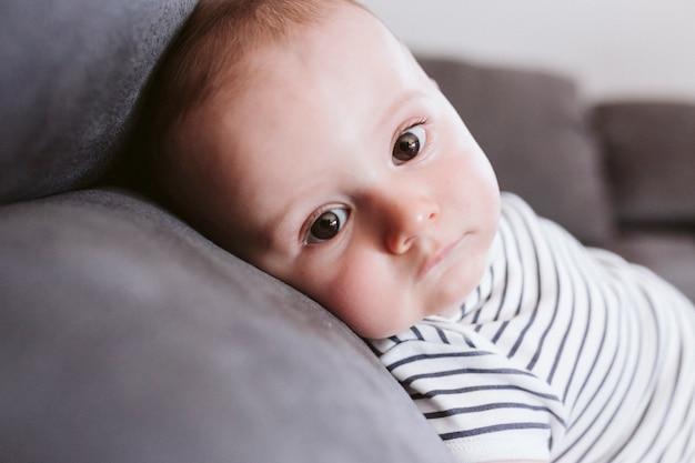 Fechar o retrato do lindo menino deitado no sofá e olhando para a câmera