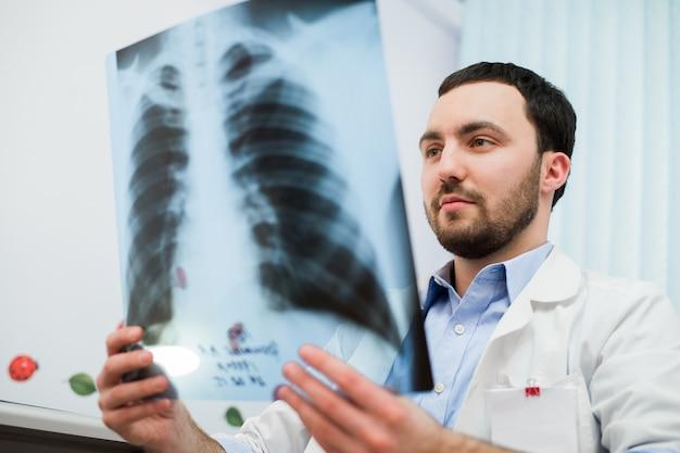 Fechar o retrato do médico olhando o raio x do tórax em seu escritório