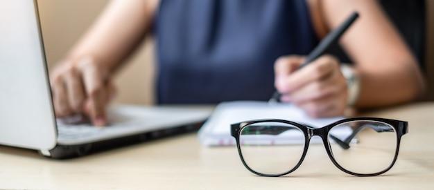 Fechar os óculos com mulher de negócios usando o laptop