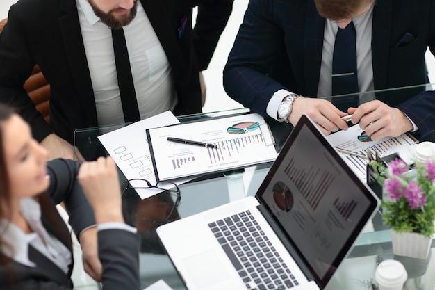 Fechar relatório financeiro na mesa da equipe de negócios