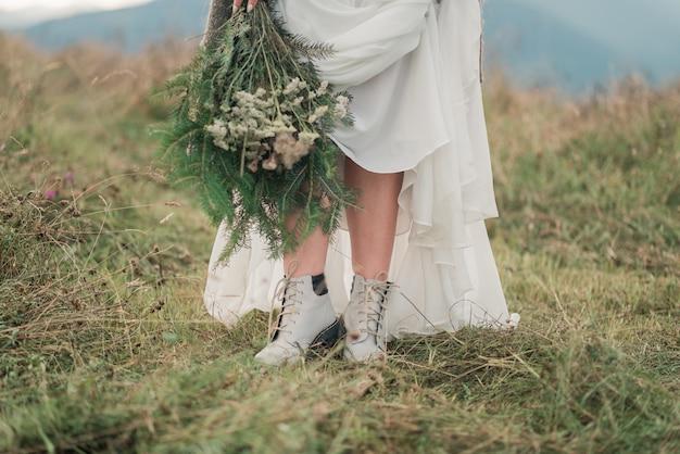 Fechar sapatos de casamento da noiva na paisagem de montanhas