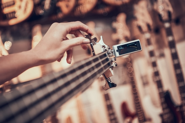 Fechar-se. a mulher afina a guitarra com o grampo do afinador, torcendo os pinos no braço da guitarra.