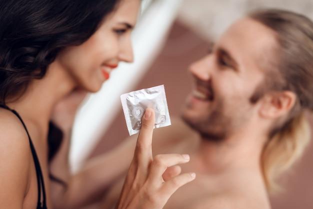 Fechar-se. a mulher apaixonado nova prende o preservativo em sua mão.