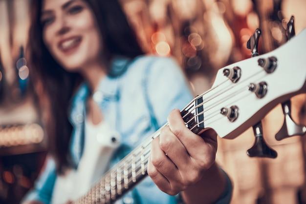 Fechar-se. a mulher prende trastes no fretboard da guitarra elétrica.