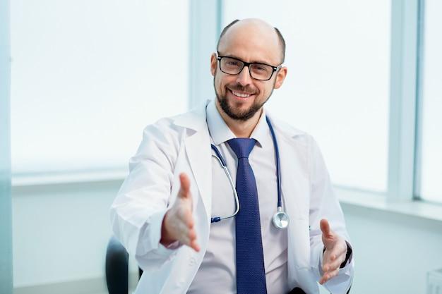 Fechar-se. amigável médico estendendo a mão para um aperto de mão.