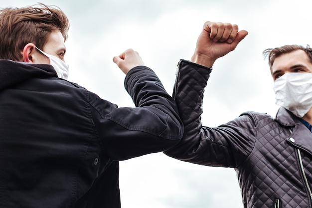 Fechar-se. amigos com máscaras protetoras cumprimentando-se. conceito de proteção à saúde