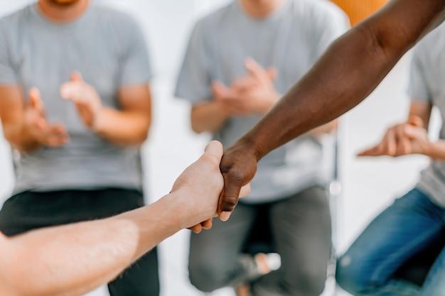Fechar-se. amigos os participantes do workshop, apertando as mãos uns dos outros. negócios e educação