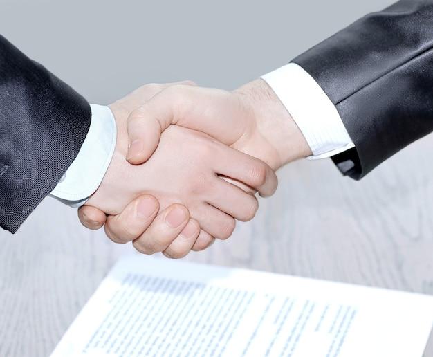 Fechar-se. aperto de mão aos parceiros de negócios após a assinatura do contrato. conceito de parceria