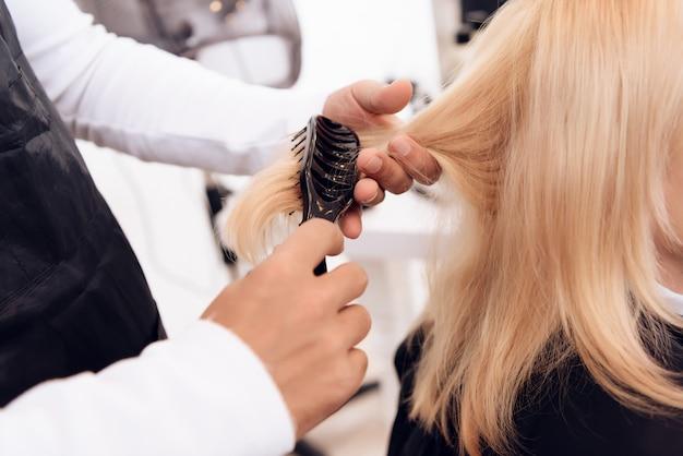 Fechar-se. as mãos do cabeleireiro penteiam para fora o cabelo louro reto.