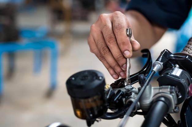 Fechar-se. as pessoas segurando a mão estão consertando uma moto use uma chave e uma chave de fenda