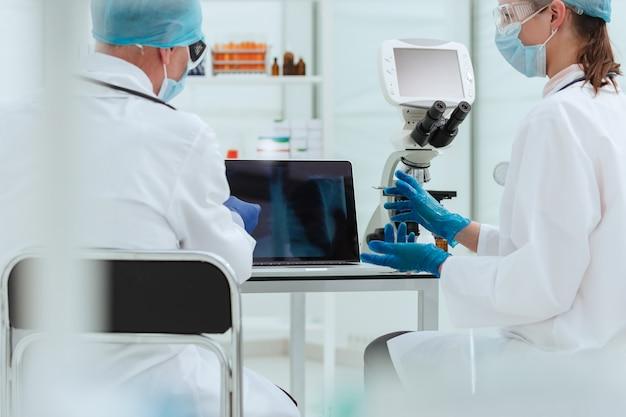 Fechar-se. atendendo médicos discutindo raios-x no laboratório.