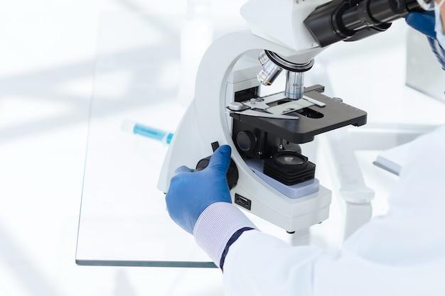 Fechar-se. biólogo cientista com uma máscara protetora, olhando através de um microscópio. ciência e proteção da saúde.