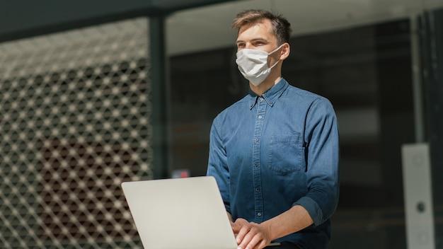 Fechar-se. blogueiro masculino com uma máscara protetora, usando um laptop na rua.