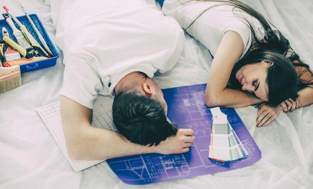 Fechar-se. casal jovem e cansado está dormindo no chão de um apartamento novo.