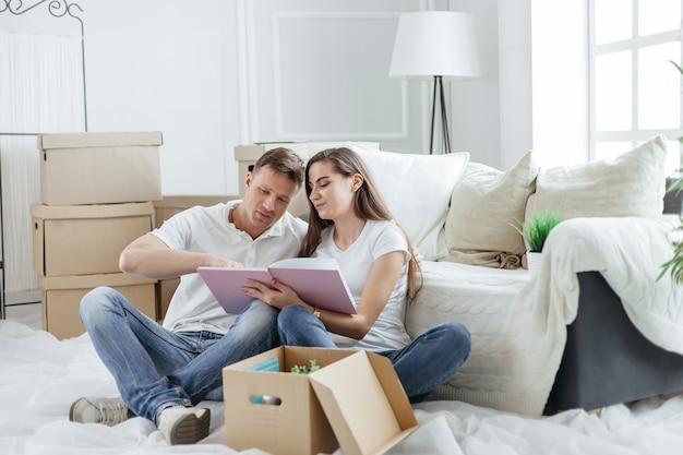 Fechar-se. casal olhando para uma foto em um álbum de fotos de família.
