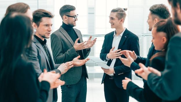 Fechar-se. chefe e equipe de negócios parabenizando seu colega