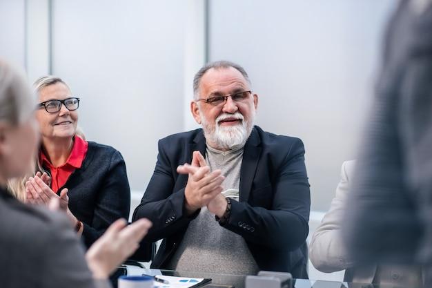 Fechar-se. chefe sorridente aplaude durante uma reunião de trabalho. conceito de negócios