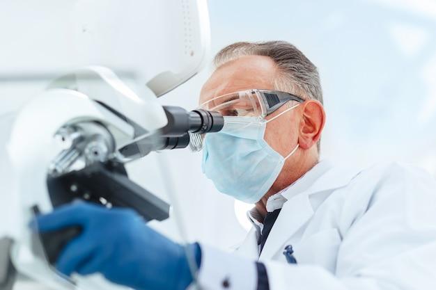Fechar-se. cientista com uma máscara protetora, olhando através de um microscópio. ciência e proteção da saúde.
