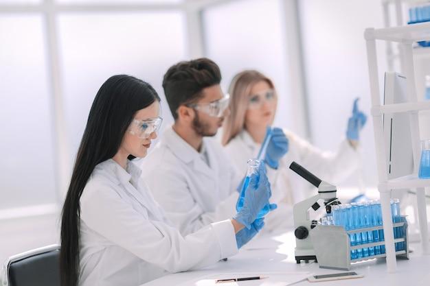 Fechar-se. cientista mulher olhando para o tubo com o líquido. ciência e saúde