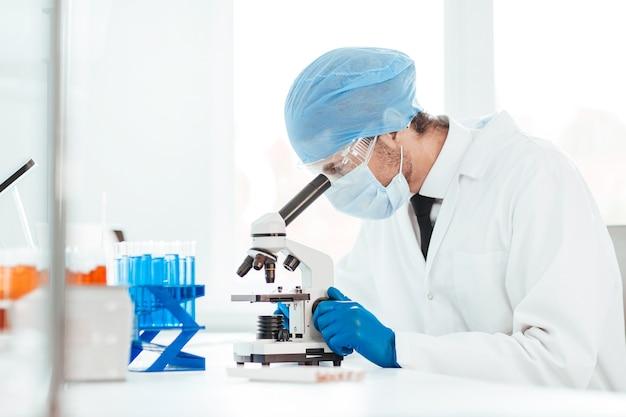 Fechar-se. cientista olhando pela ocular de um microscópio. foto com uma cópia-espaço.