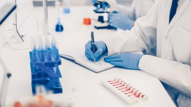 Fechar-se. cientista registrando os resultados do estudo em um diário de laboratório. foto com uma cópia-espaço.
