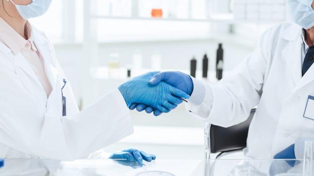 Fechar-se. cientistas da microbiologia apertando as mãos. ciência e saúde.