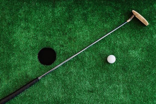 Fechar-se. clube de golfe e bola de golfe em um campo de minigolfe
