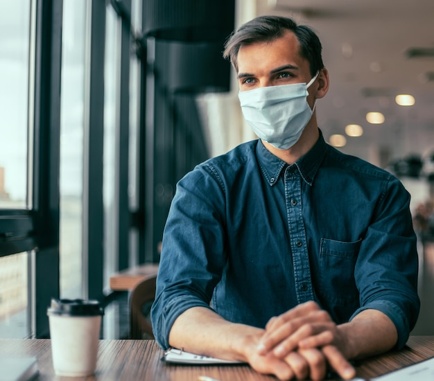 Fechar-se. colegas de trabalho com máscaras protetoras, trabalhando com documentos financeiros.