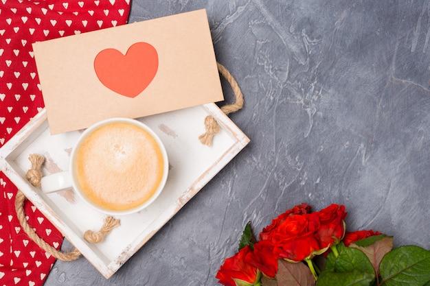 Fechar-se. conceito dia dos namorados. café da manhã, envelope com coração, rosas na mesa cinza. espaço livre. espaço para texto.