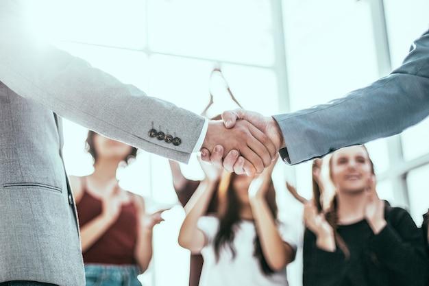 Fechar-se. confiante jovem empresário apertando as mãos de parceiro de negócios.