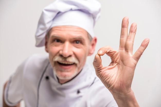 Fechar-se. cozinheiro chefe masculino sênior no uniforme que gesticula está bem.