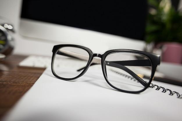 Fechar--se de óculos de leitura na mesa de escritório