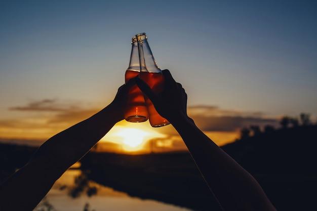 Fechar-se. duas mãos, duas garrafas cor de rosa. coquetel, suco, ao pôr do sol, ao ar livre