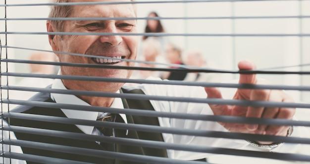 Fechar-se. empregado de escritório alegre olhando pelas cortinas da janela. conceito de negócios