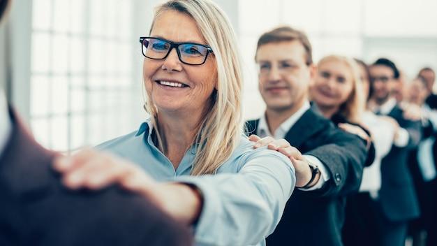 Fechar-se. empresária feliz em pé na frente de sua equipe de negócios. o conceito de trabalho em equipe