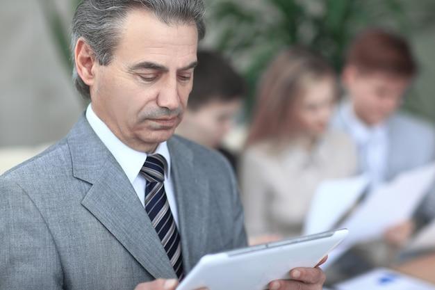 Fechar-se. empresário moderno olhando para a tela do tablet digital. foto no fundo desfocado do escritório