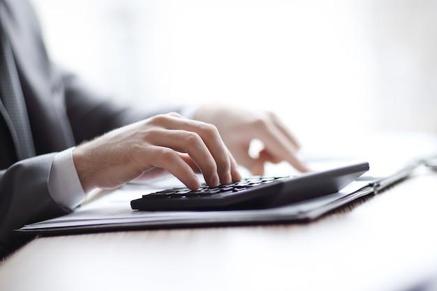Fechar-se. empresário pode usar a calculadora para calcular o lucro.