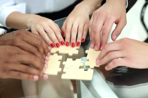 Fechar-se. equipe de negócios com peças de quebra-cabeça atrás de uma mesa