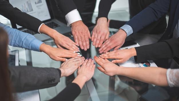 Fechar-se. equipe de negócios fazendo um círculo com as palmas das mãos. o conceito de trabalho em equipe