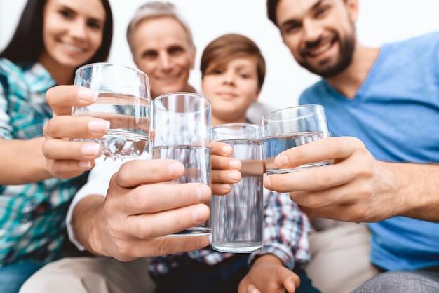 Fechar-se. família alegre torcendo com copos de água.