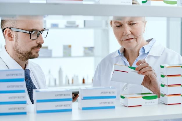 Fechar-se. farmacêuticos discutindo um pedido online perto de uma vitrine de farmácia.